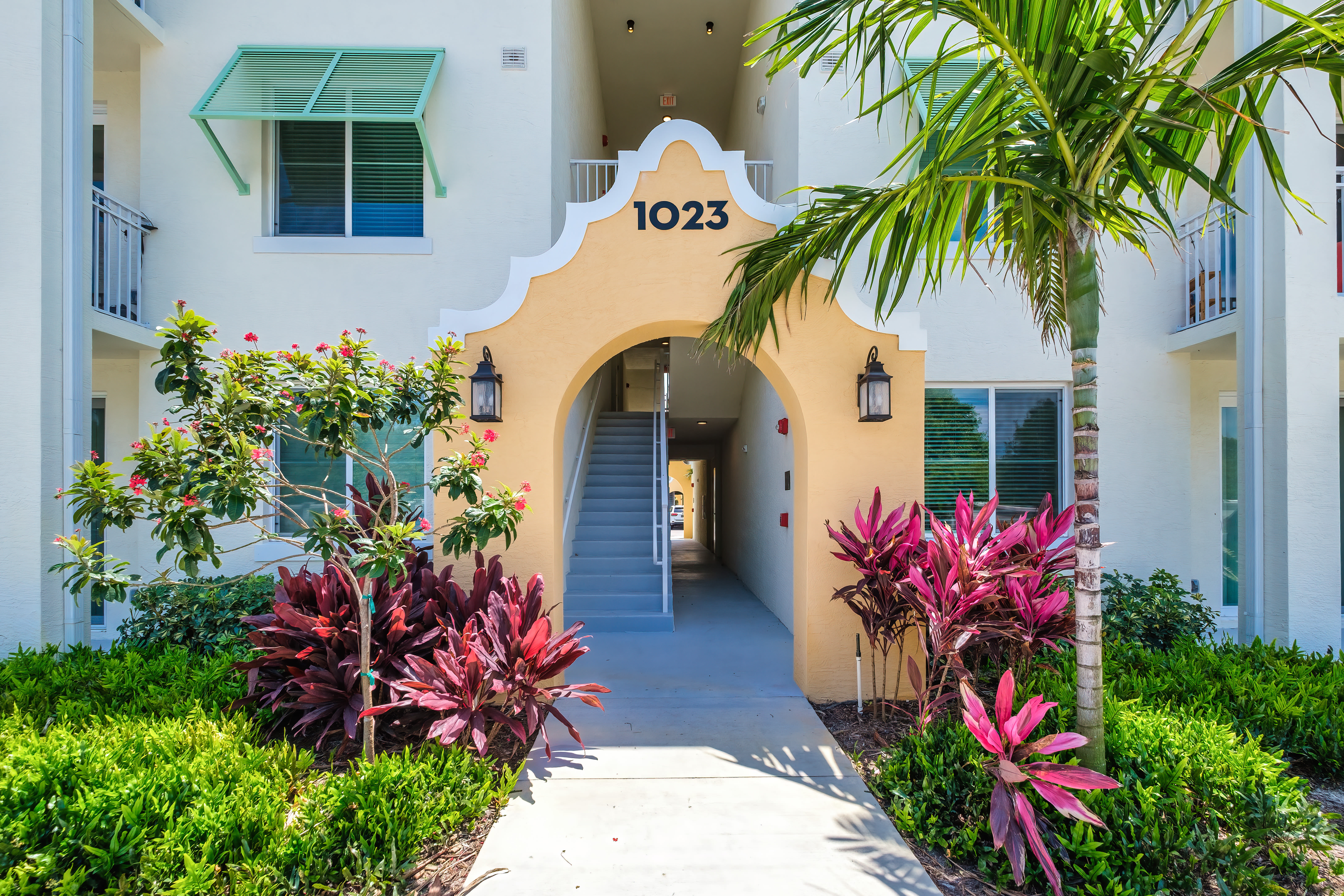 Arched entryway surrounded by lush landscaping at Town Lantana in Lantana, Florida