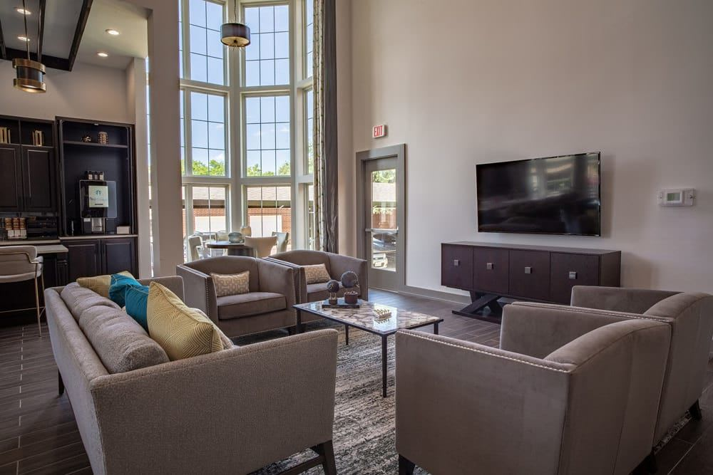lounge area with a tv and several plush chairs arranged around a coffee table at The Spring at Silverton in Fort Worth, Texas