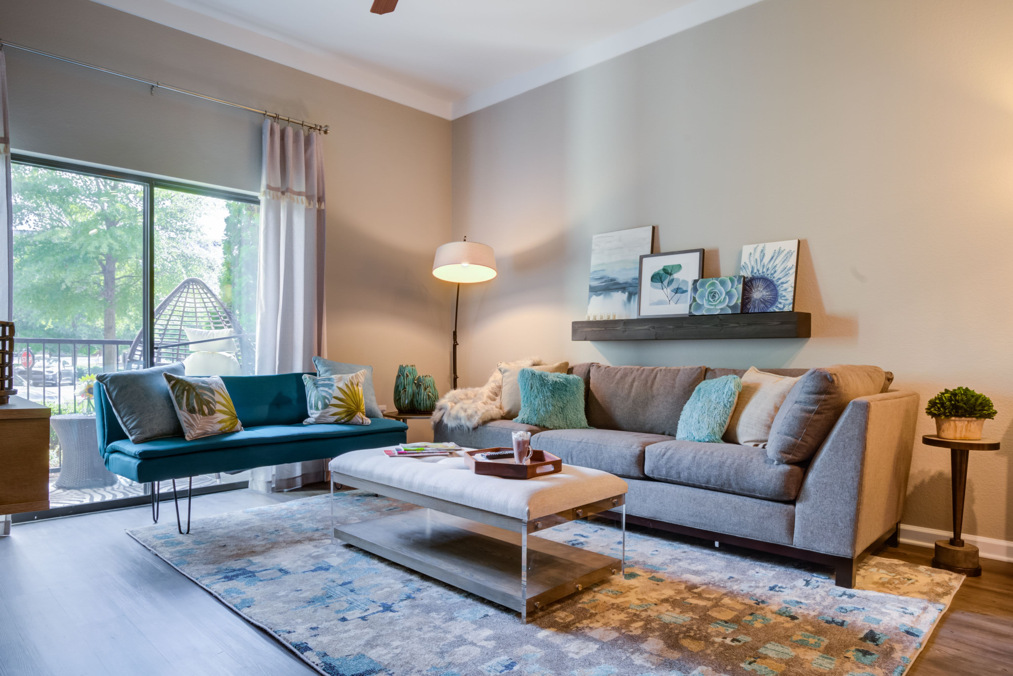 Model living room with door to balcony at Celsius Apartment Homes in Charlotte, North Carolina