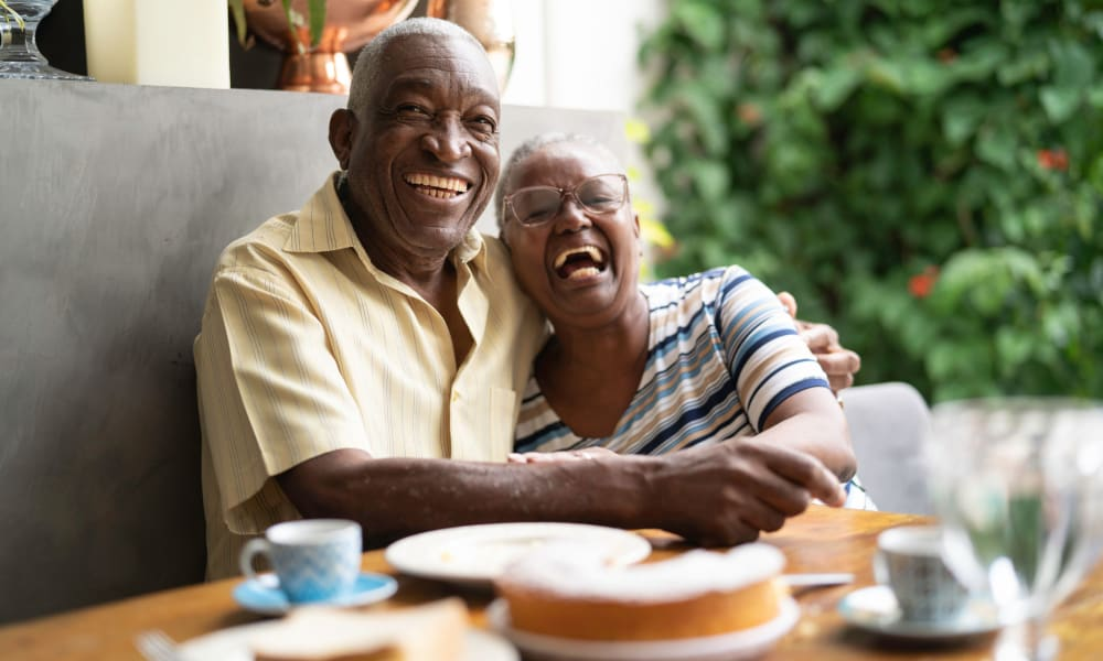 Resident couple hugging at a table in Randall Residence of Sterling Heights in Sterling Heights, Michigan
