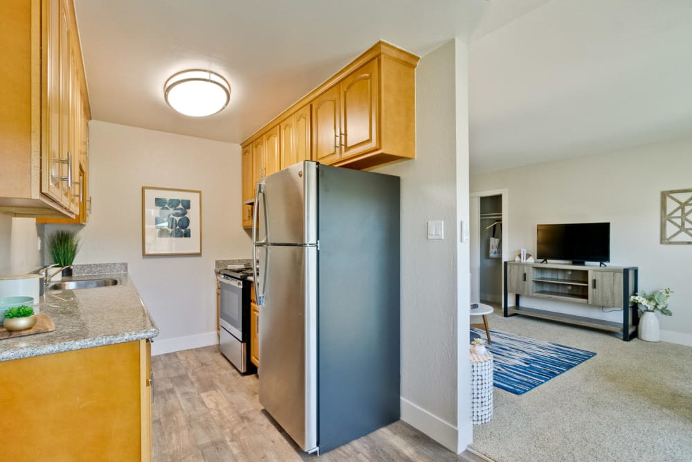 Modern kitchen with custom cabinetry & stainless-steel appliances at Mosaic Hayward in Hayward, California