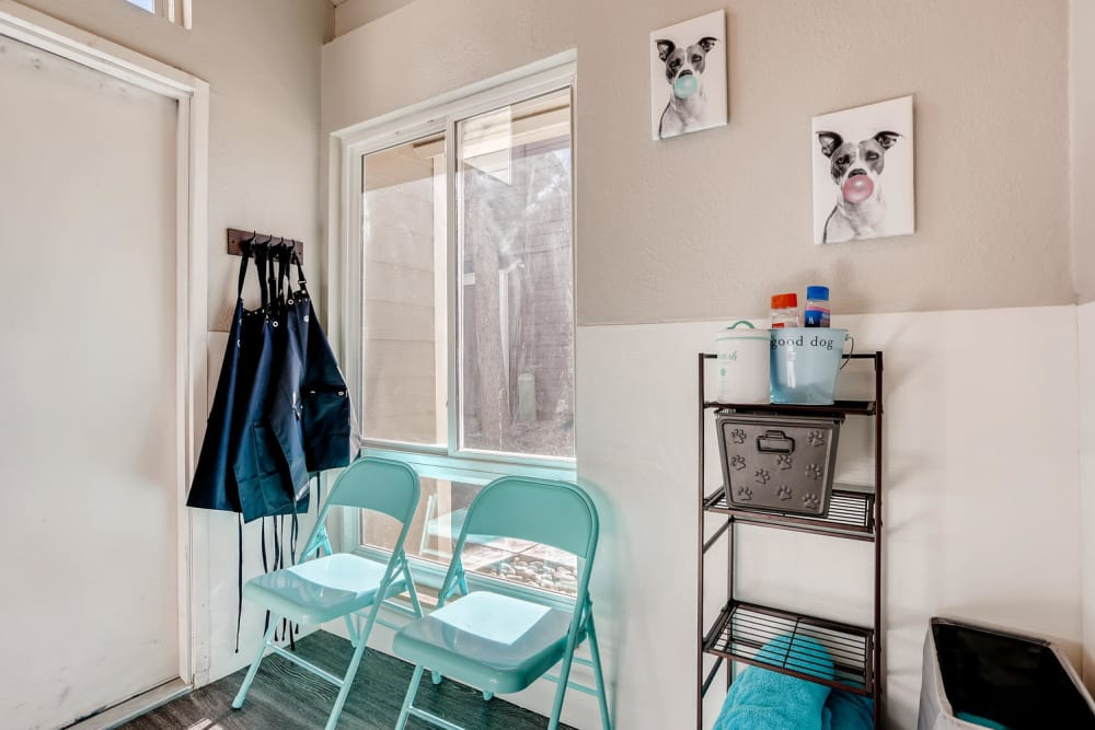 Pet Spa wash supply area with folding chairs aprons hanging on wall and window at The Ranch at Bear Creek Apartments & Townhomes in Lakewood, Colorado