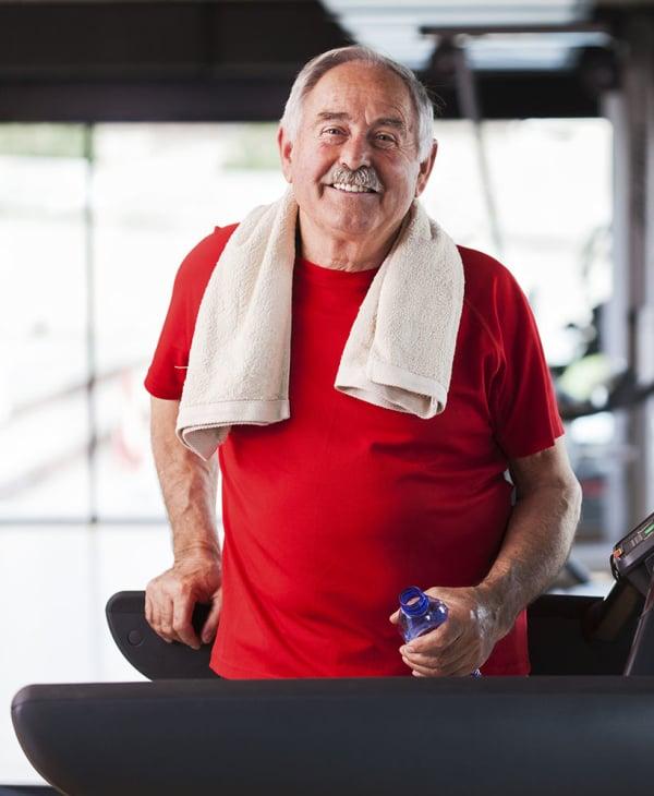 Senior living resident using the fitness center at Oxford Villa Active Senior Apartments