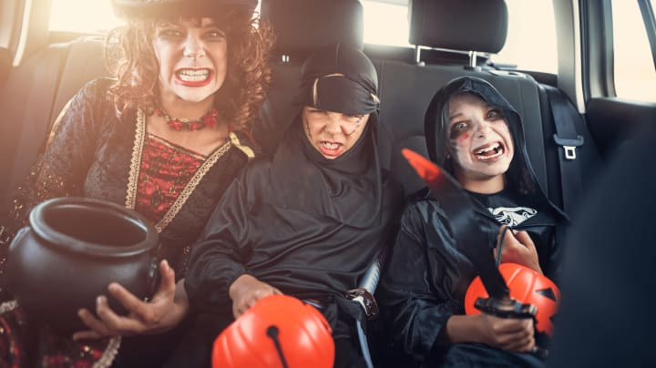 people in costumes riding in car