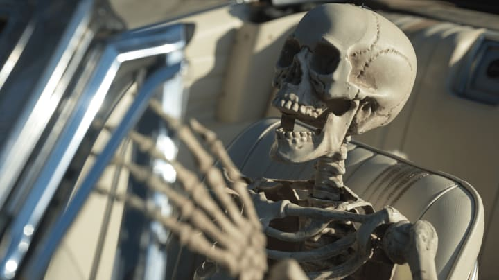 skelton in driver's seat of convertible