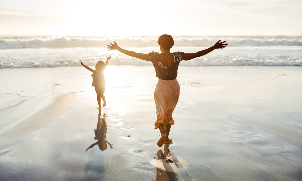 Mother and daughter playing on the beach near Mediterranean Village Apartments in Costa Mesa, California
