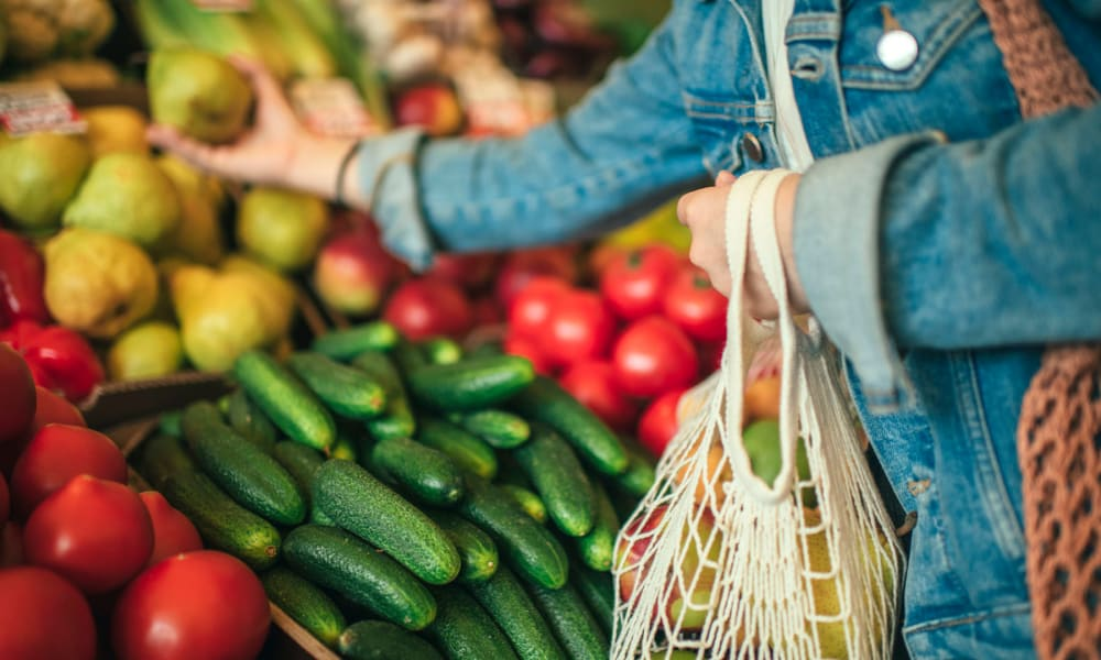 Resident shopping for fresh produce at a farmers market near West Park Village in Los Angeles, California
