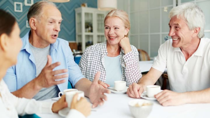 Group of four seniors chatting over coffee