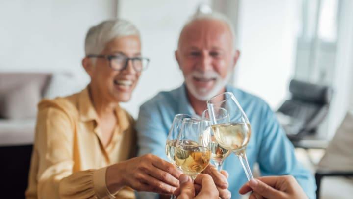 Seniors clinking wine glasses