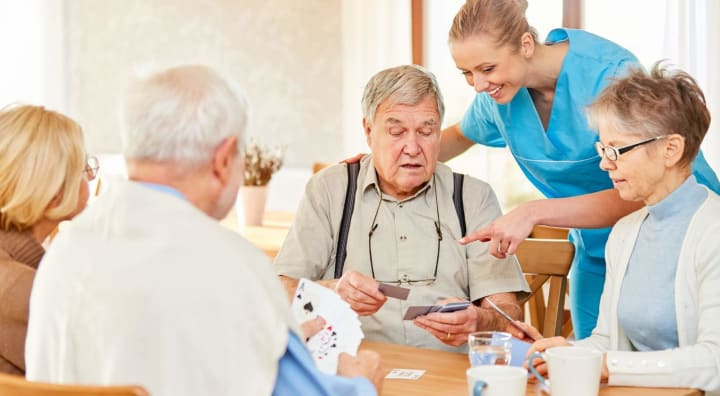 Two senior couples playing cards together with caregiver