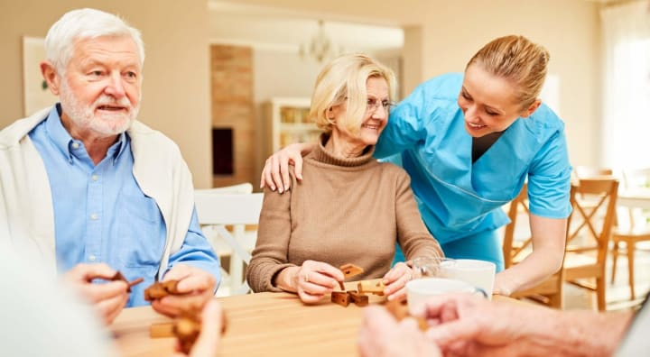Senior couple doing activity with caregiver looking on