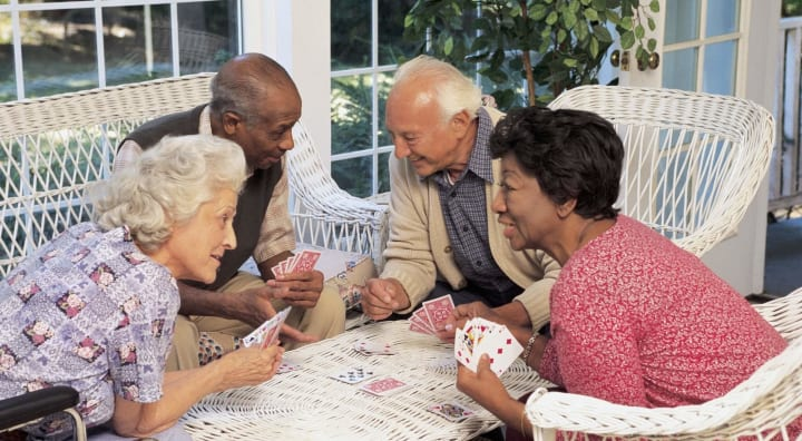 Two couples of seniors playing cards together