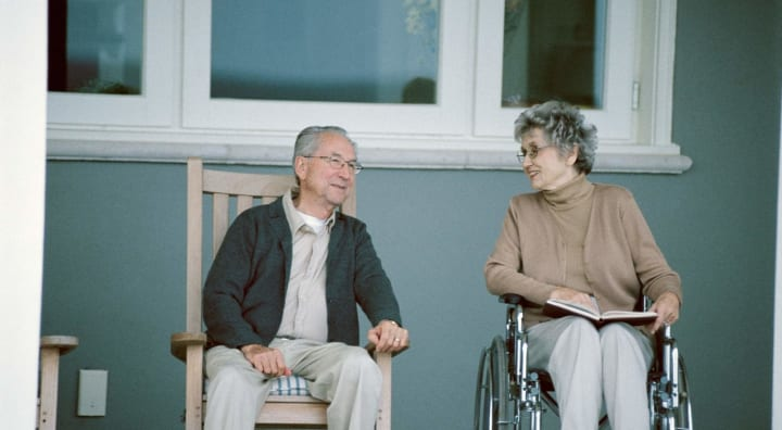 Two seniors sitting on porch chatting