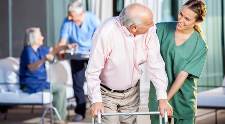 Caregiver assisting senior man on walker