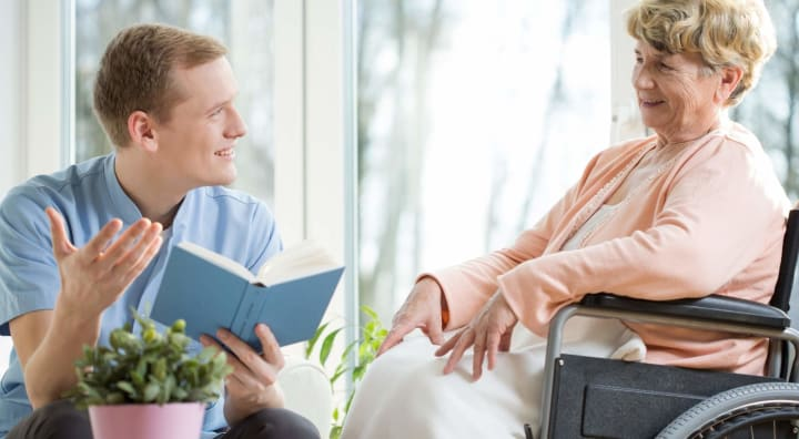 Caregiver reading to senior woman in wheelchair
