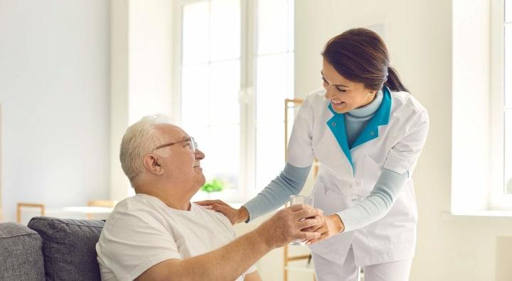 Caregiver handing senior man a glass of water