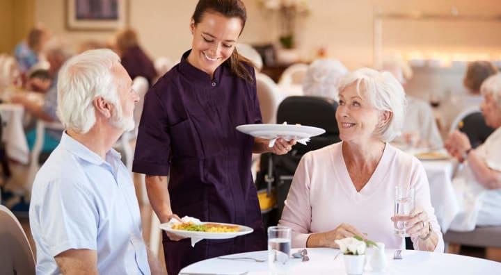 Server serving food to senior couple