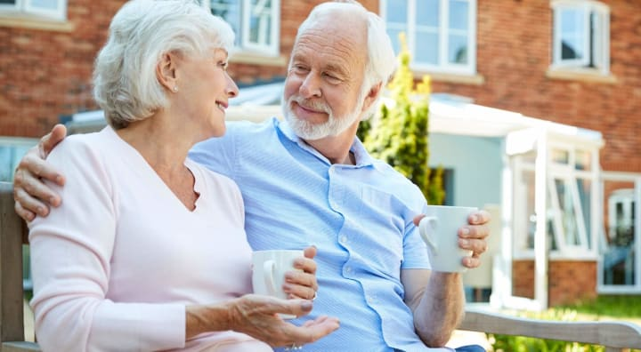 Senior couple enjoying coffee on a bench