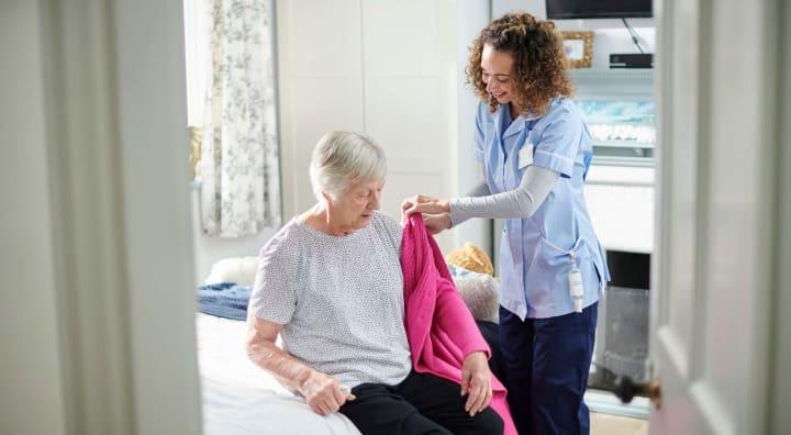 Caregiver assisting senior woman with cardigan
