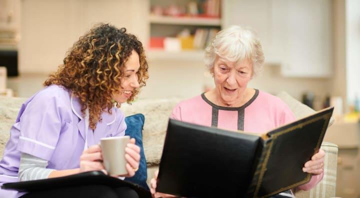 Senior woman showing her caregiver a photo album