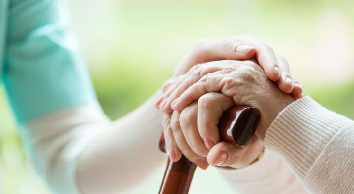 Caregiver holding hands of senior and walking stick