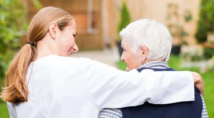 Caregiver with arm around senior woman