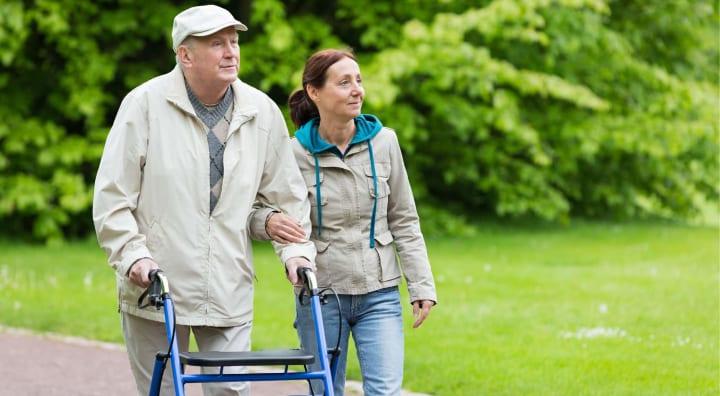 Senior man walking outside with caregiver