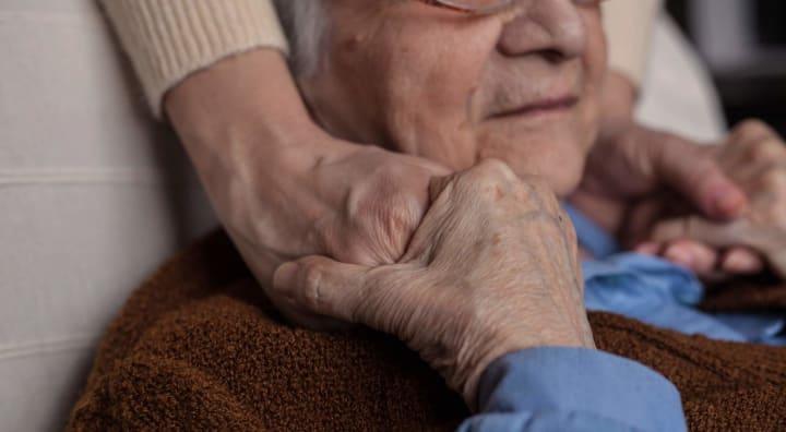 Senior man holding hands of someone off-camera