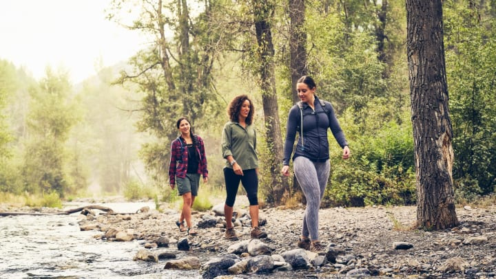 A group of three young women hiking in a wilderness area.