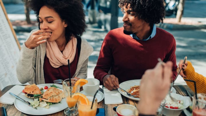 A man and a woman sitting outside at a shared table, eating brunch.