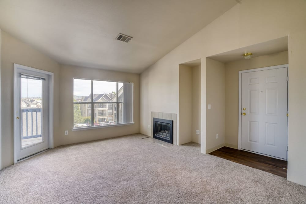Vacant living room with fireplace at The Pines at Castle Rock Apartments in Castle Rock, Colorado