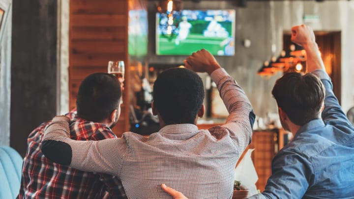 Resident friends cheering for their favorite team together on the flatscreen TV in the clubhouse at Union at Carrollton Square in Carrollton, Texas