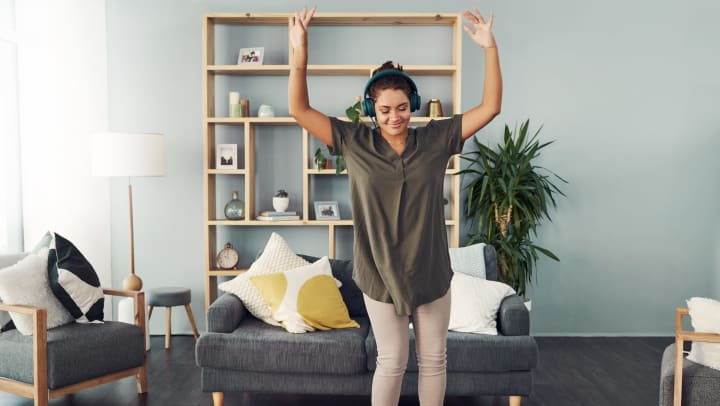 A happy young woman using headphones and dancing in the living room at home.