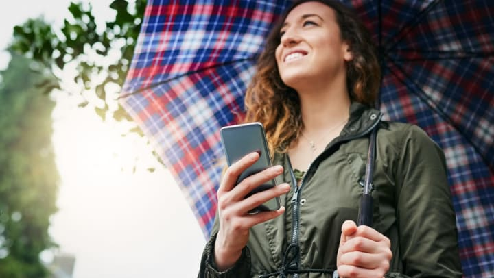 A smiling young woman holds a phone in one hand while standing under the open umbrella she is holding in her other hand.