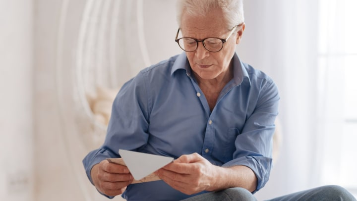 Elderly man with glasses sitting down and looking at an envelope.