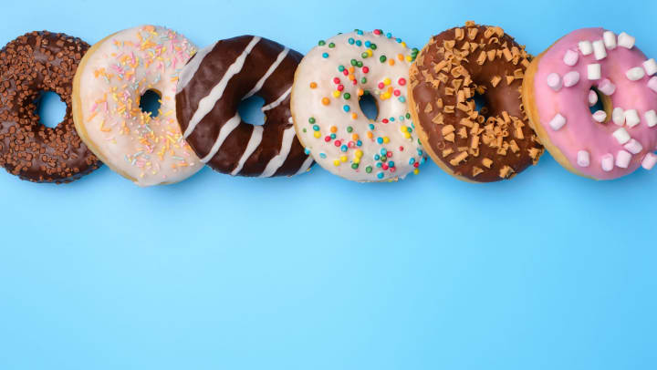A series of colorful assorted donuts on a light blue background.