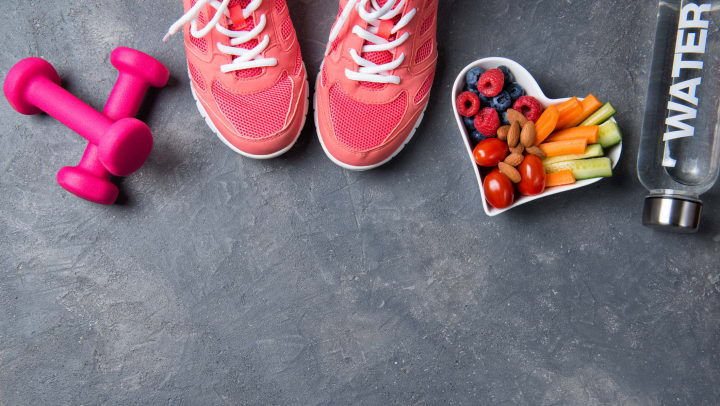 Pink sneakers, dumbbells, bottle of water and a heart-shaped plate with vegetables and berries on a gray background