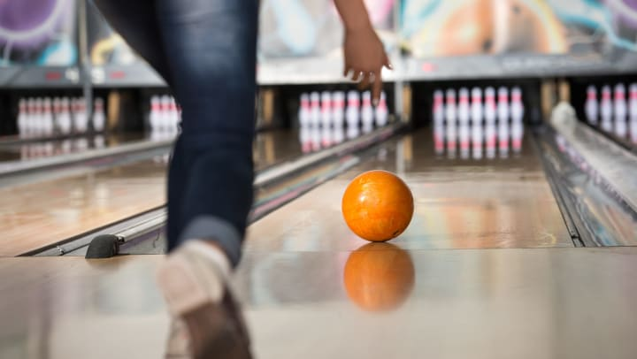 Close-up view from behind as a person at a bowling alley throws an orange bowling ball toward the pins.