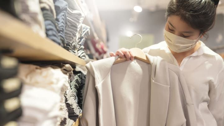 Woman browsing clothes in boutique shop.