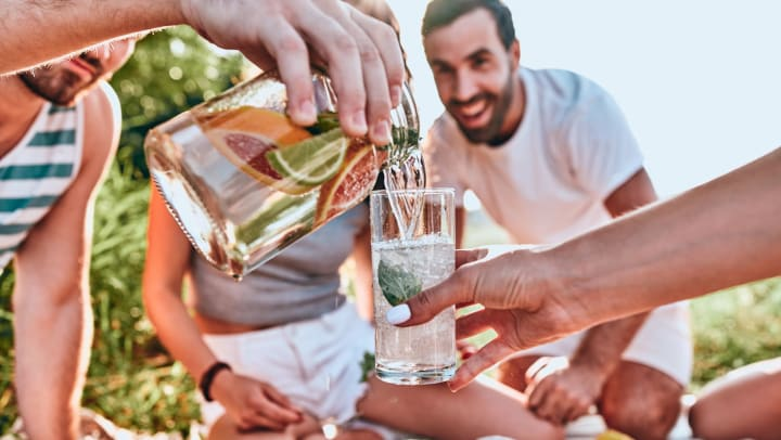 Man pouring beverage into woman's glass at an outdoor party.