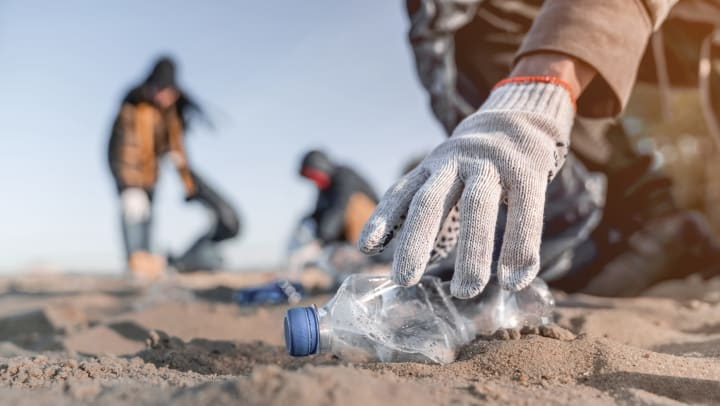 The gloved hand of a volunteer picking up trash on a beach.