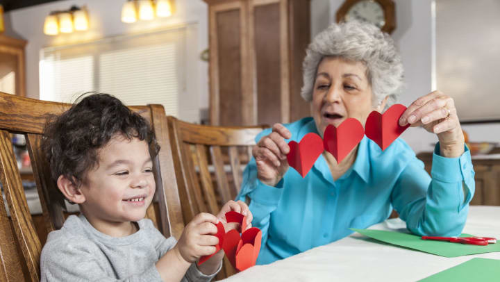 A young boy makes paper hearts with his grandmother for Valentine's Day.