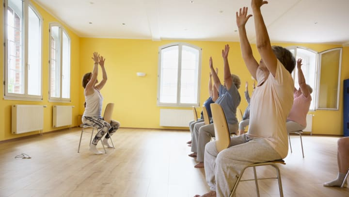 A teacher and senior women on chairs practicing yoga.