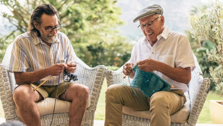 Two senior men sitting in armchairs and knitting.