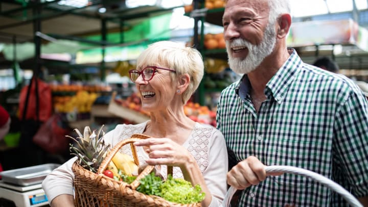 A smiling, older man and woman carry baskets of fruits and vegetables at a farmers market.