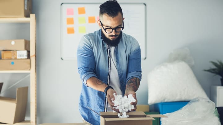 Man pouring packing peanuts into a cardboard box.