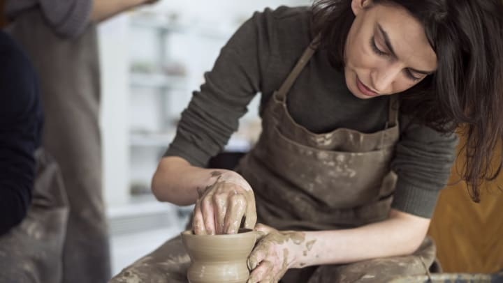 Resident throwing a pot on the wheel in a ceramics class near Olympus Town Center in Keller, Texas