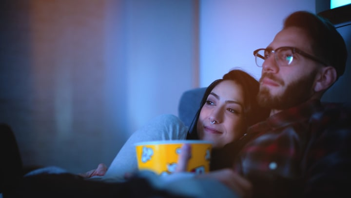 Young couple watching a movie with popcorn in their apartment at Redstone at SanTan Village in Gilbert, Arizona.