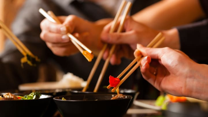 Friends enjoying food with chopsticks