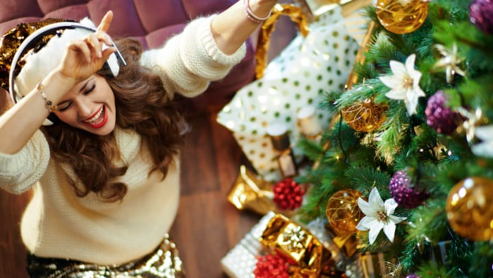 Woman dancing with headphones on around her Christmas tree